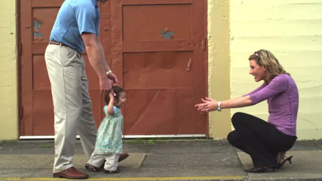 Una-madre-y-un-padre-ayudar-a-su-hija-a-caminar-por-la-calle