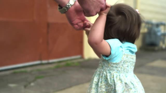 Una-feliz-niña-sonriente-camina-por-la-calle-con-la-ayuda-de-un-adulto
