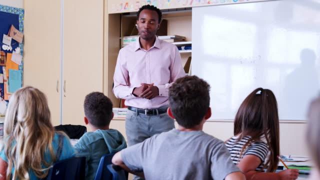 Profesor-habla-a-los-alumnos-en-clase-en-la-escuela-primaria
