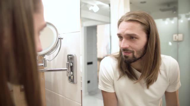 Bathroom-Man-Looking-In-Mirror-And-Touching-Face