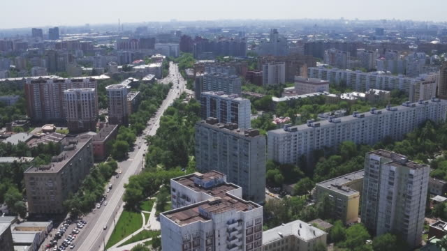 Panoramic-aerial-view-of-one-of-the-districts-of-Moscow-with-residential-buildings-playgrounds-kindergarten-and-road-traffic-summer-weather-Urban-cityscape-from-quadrocopter