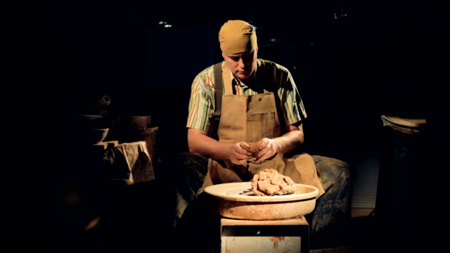 A-potter-in-a-dark-room-kneads-clay-