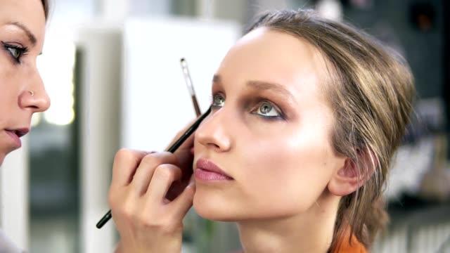 Studio-machen-Professionelle-Make-up-Künstler-machen-sich-für-ein-schönes-kaukasischen-Modell-zu-tun-Einige-Lidschatten-mit-einem-Pinsel-auftragen-Augen-Make-up