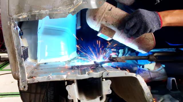 Soldar-acero-con-electricidad-en-taller-de-reparación-de-cuerpo-de-auto-closeup