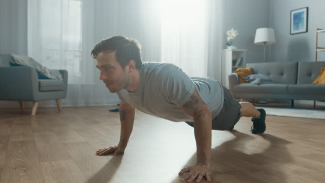 Athletic-Fit-hombre-en-camiseta-y-pantalones-cortos-es-haciendo-Push-Up-ejercicios-en-casa-en-su-amplio-y-luminoso-apartamento-con-Interior-minimalista-