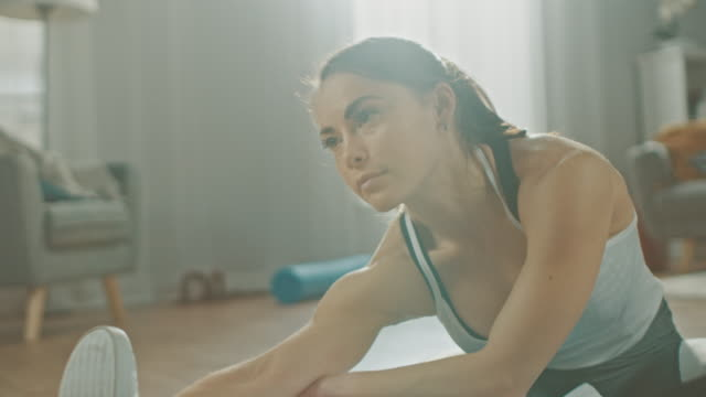 Close-Up-of-a-Beautiful-Confident-Fitness-Girl-in-an-Athletic-Workout-Clothes-Doing-Stretching-Yoga-Exercises-in-Her-Bright-and-Spacious-Living-Room-with-Cozy-Minimalistic-Interior-