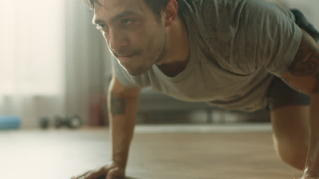 Slow-Motion-Close-Up-of-a-Muscular-Fit-Man-in-T-shirt-and-Shorts-is-Doing-Mountain-Climbers-While-Using-a-Stopwatch-on-His-Phone-He-is-Training-at-Home-in-His-Apartment-with-Minimalistic-Interior-