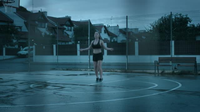 Hermosa-chica-Fitness-deportivo-Top-deportivo-negro-y-pantalones-cortos-es-saltan/salto-de-cuerda-Ella-está-haciendo-un-entrenamiento-en-una-cancha-de-baloncesto-al-aire-libre-cercado-Vista-desde-detrás-de-la-valla-Noche-después-de-la-lluvia-