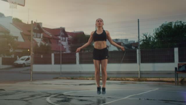 Hermoso-gimnasio-energética-chica-saltando/saltar-cuerda-Ella-está-haciendo-un-entrenamiento-en-una-cancha-de-baloncesto-al-aire-libre-cercado-Tomas-por-la-tarde-después-de-la-lluvia-