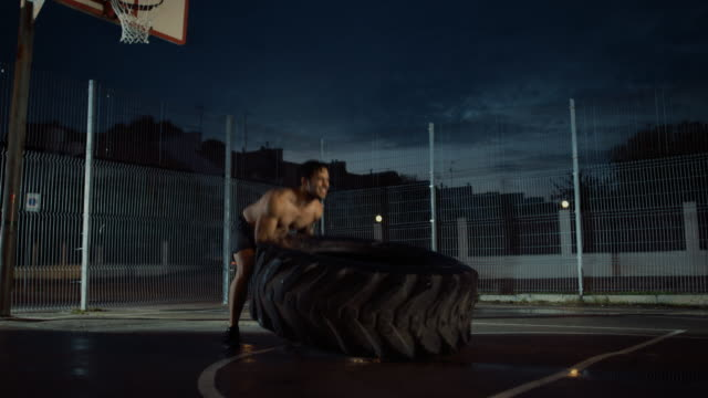 Strong-Muscular-Fit-Young-Shirtless-Man-is-Doing-Exercises-in-a-Fenced-Outdoor-Basketball-Court-He-s-Flipping-a-Big-Heavy-Tire-in-an-Afternoon-After-Rain-in-a-Residential-Neighborhood-Area-
