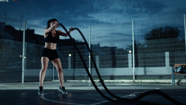 Beautiful-Energetic-Fitness-Girl-Doing-Exercises-with-Battle-Ropes-She-is-Doing-a-Workout-in-a-Fenced-Outdoor-Basketball-Court-Evening-Footage-After-Rain-in-a-Residential-Neighborhood-Area-