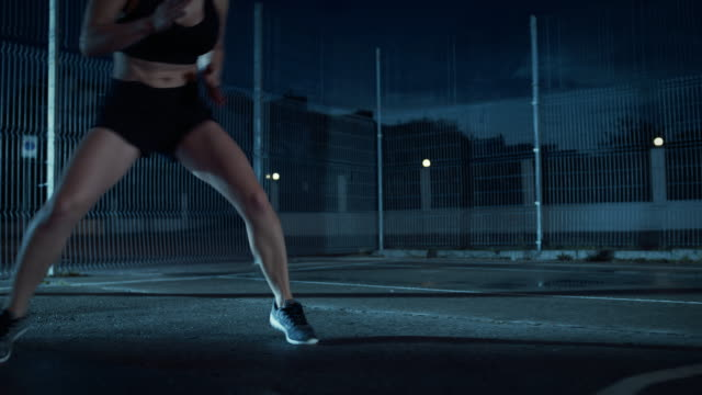 Close-Up-of-a-Beautiful-Energetic-Fitness-Girl-Doing-Footwork-Running-Drill-She-is-Doing-a-Workout-in-a-Fenced-Outdoor-Basketball-Court-Night-Footage-After-Rain-in-a-Residential-Neighborhood-Area-
