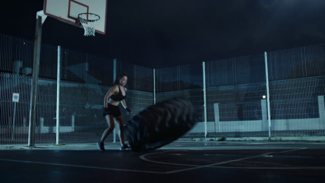 Beautiful-Energetic-Fitness-Girl-is-Doing-Exercises-in-a-Fenced-Outdoor-Basketball-Court-She-s-Flipping-a-Big-Heavy-Tire-in-a-Foggy-Night-After-Rain-in-a-Residential-Neighborhood-Area-