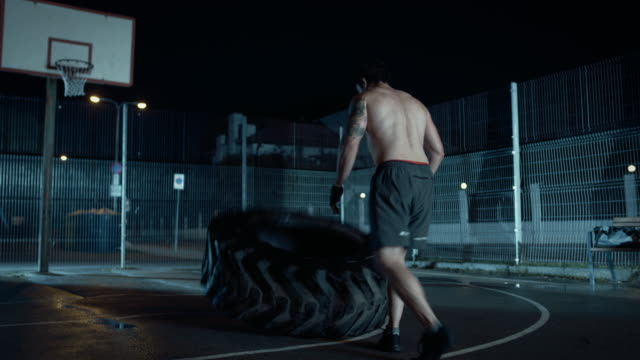 Backshot-of-a-Strong-Muscular-Fit-Young-Shirtless-Man-Doing-Exercises-in-a-Fenced-Outdoor-Basketball-Court-He-s-Flipping-a-Big-Heavy-Tire-in-a-Night-After-Rain-in-a-Residential-Neighborhood-Area-
