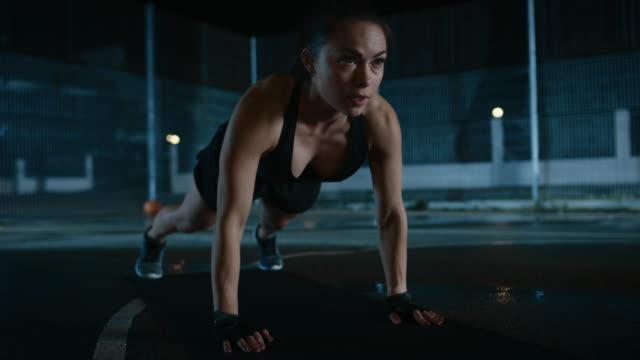 Agotado-el-gimnasio-deportivo-hermosa-chica-haciendo-Push-Up-ejercicios-Ella-está-haciendo-un-entrenamiento-en-una-cancha-de-baloncesto-al-aire-libre-cercado-Imágenes-de-la-noche-después-de-la-lluvia-en-una-zona-residencial-del-barrio-