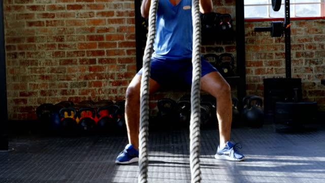 Senior-hombre-haciendo-crossfit-entrenamiento-de-cuerda-en-el-gimnasio-4k