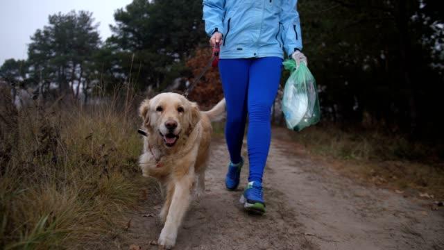 Corredor-femenino-recogiendo-basura-en-el-bosque-del-otoño