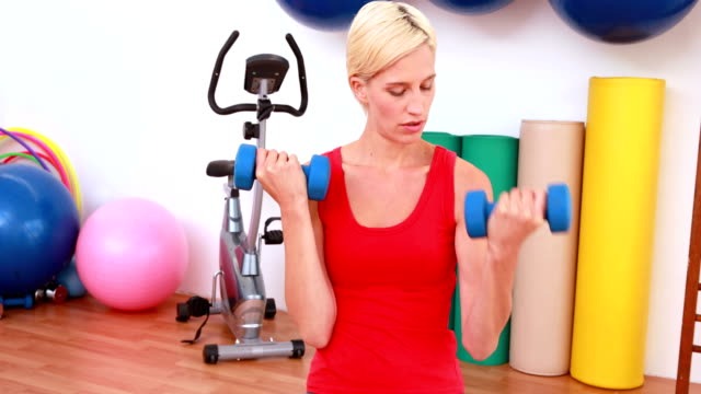Blonde-woman-lifting-dumbbells-on-exercise-ball