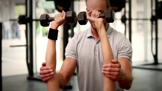 Fit-woman-lifting-dumbbells-with-trainer
