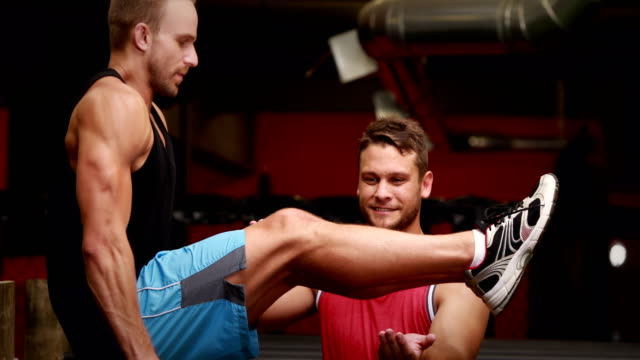 Trainer-helping-client-to-l-hang-in-gym-gym