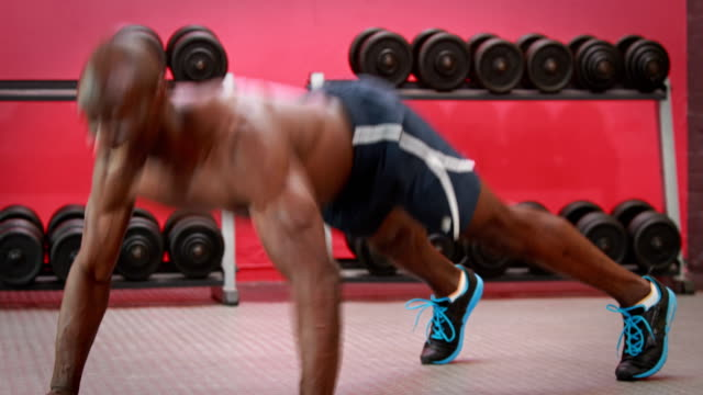 Muscular-man-doing-press-up-claps-at-gym