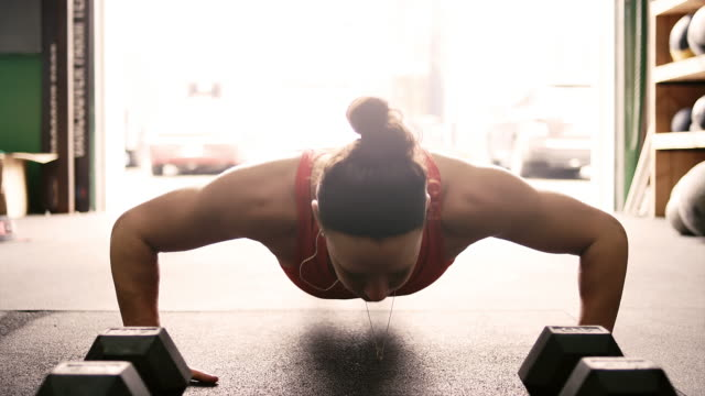 Close-up-of-a-fit-young-woman-doing-pushups-and-listening-to-music-and-then-looking-at-the-camera