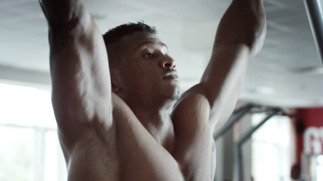 Man-execute-pull-ups-in-gym
