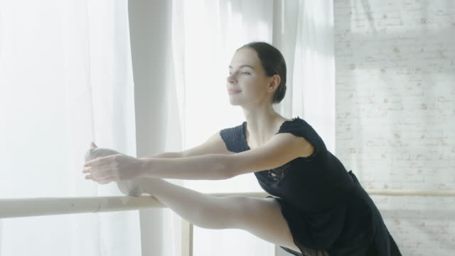 Close-up-of-a-Young-and-Beautiful-Ballerina-Doing-Leg-Stretching-at-the-Barre-Shot-on-a-Sunny-Morning-in-a-Spacious-and-Light-Studio-In-Slow-Motion-