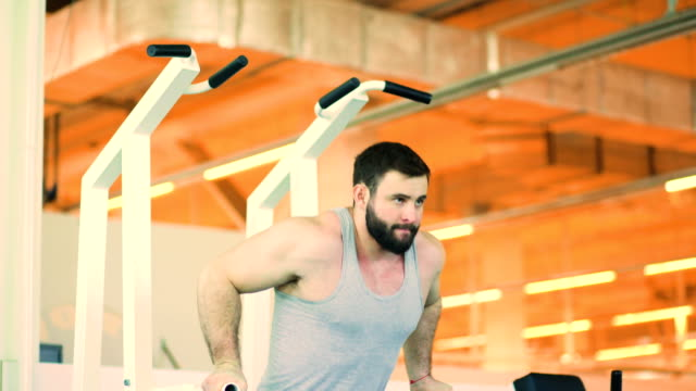 Guapo-hombre-deportivo-está-haciendo-ejercicio-en-el-gimnasio-y-el-gimnasio