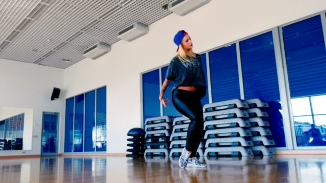 Pretty-girl-in-cap-dancing-the-modern-dance-in-gym