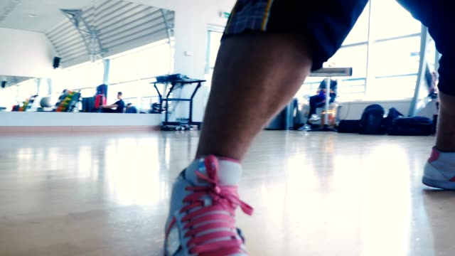 Close-up---the-man-in-sneakers-dancing-in-the-gym