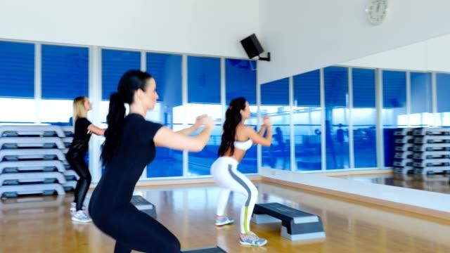 Tres-atractivas-mujeres-entrenando-las-nalgas-y-las-piernas-en-el-gimnasio-delante-del-espejo