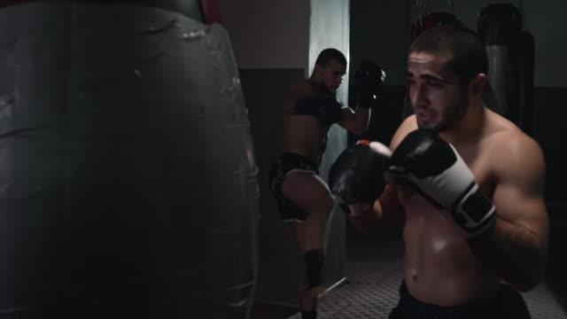 Zwei-Athleten-zu-bekämpfen-Training-mit-Punch-Taschen