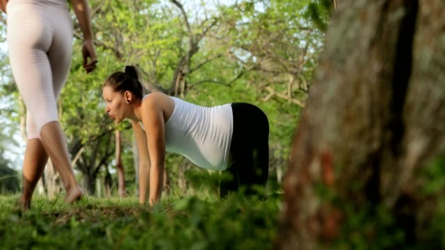 Yoga-Trainer-Helping-Pregnant-Woman-With-Exercise-For-Backpain