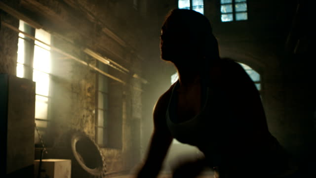 Strong-Athletic-Woman-Exercises-with-Battle-Ropes-as-Part-of-Her-Fitness-Gym-Workout-Routine-She-s-Covered-in-Sweat-and-Training-Takes-Place-in-a-Abandoned-Factory-Remodeled-into-Gym-