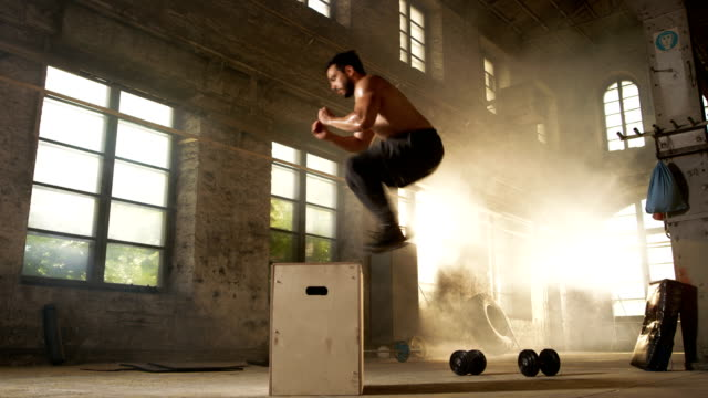 Athletic-Shirtless-Fit-Man-Energetically-Box-Jumps-in-Hardcore-Gym-doing-Part-of-Cross-Fitness-Training-Program-Man-is-Sweaty-from-Intense-Workout/-Exercise-Gym-is-in-Industrial-Factory-Location-