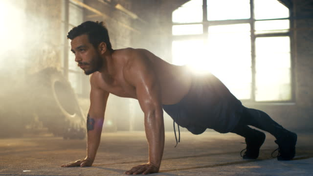 Muscular-Shirtless-Man-Covered-in-Sweat-Does-Push-ups-in-a-Deserted-Factory-Remodeled-into-Gym-Part-of-His-Fitness-Workout/-High-Intensity-Interval-Training-