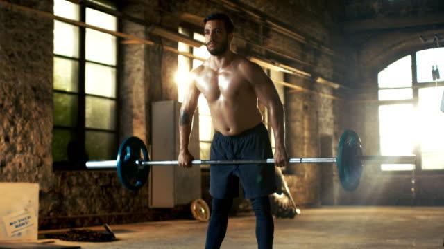 Hombre-sin-camisa-atlética-fuerte-ascensores-con-barras-pesadas-como-parte-de-la-rutina-de-entrenamiento-de-Fitness-Gimnasio-es-en-fábrica-remodelada-