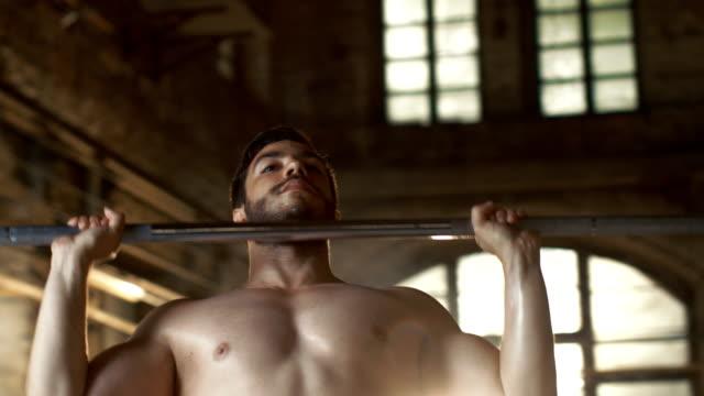 Primer-plano-de-un-hombre-sin-camisa-Muscular-elevación-pesada-barra-y-hacer-ejercicio-de-culturismo-de-Press-militar-en-el-edificio-de-gimnasio-Industrial-