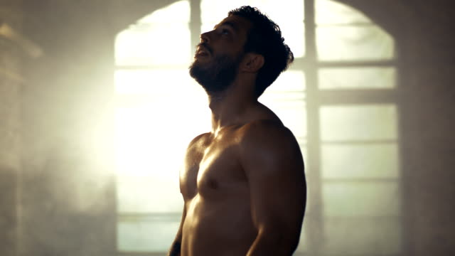 Handsome-Shirtless-Man-with-Naked-Muscular-Torso-with-Visible-Six-Pack-Stands-Resting-after-Bodybuilding-Exercise-He-Wipes-Sweat-from-His-Forehead-He-s-in-the-Middle-of-Abandoned-Factory-Building-