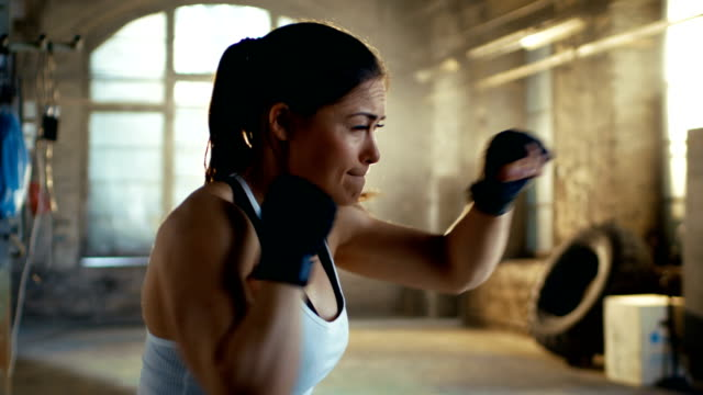 Beautiful-Athletic-Woman-Punches-Air-with-Her-Fists-as-Part-of-Her-Intensive-Cross-Fitness-Gym-Training-