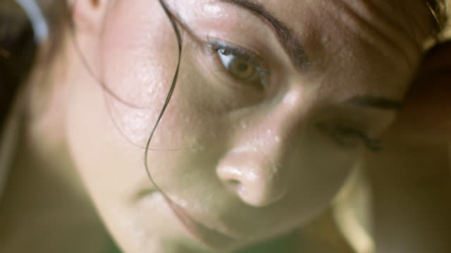 Close-up-foto-de-una-hermosa-mujer-atlética-limpia-sudor-de-su-frente-con-una-mano-mira-a-cámara-Está-cansada-después-de-intensivos-Cross-Fitness-ejercicio-