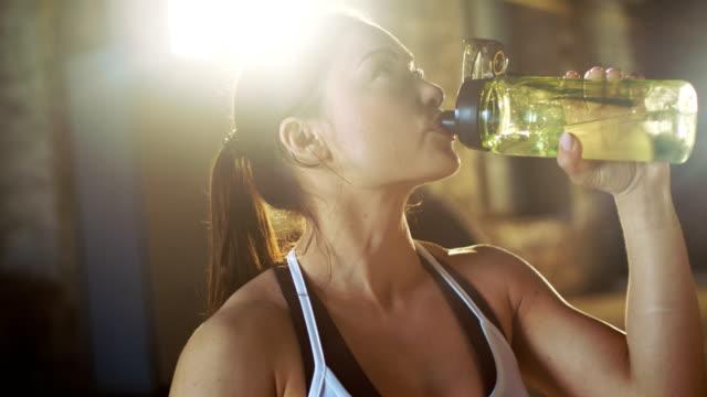 Starke-sportliche-Frau-Getränke-aus-einer-Wasserflasche-nach-anstrengenden-Cross-Fitness-Bodybuilding-Training-in-ihrem-Lieblings-Turnhalle-