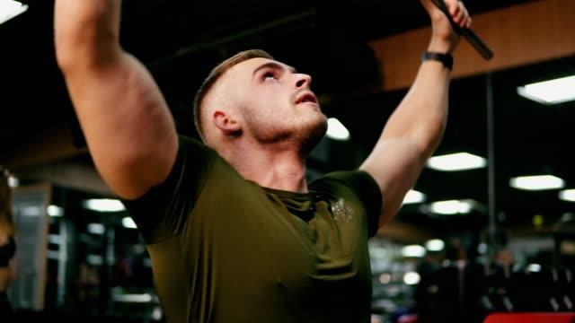 Joven-rubia-guapa-hombre-iexercising-sus-músculos-del-pecho-y-los-hombros-en-el-gimnasio-de-entrenamiento-Rodada-en-4k