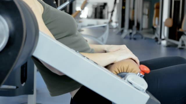 Mujer-hace-empuja-para-las-nalgas-en-el-aparato-de-entrenamiento