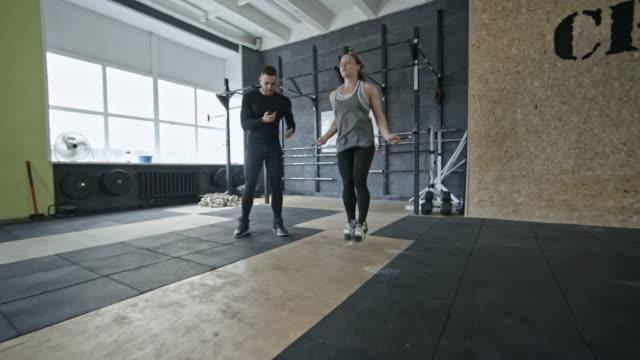 Mujer-haciendo-saltar-cuerda-ejercicio-con-entrenador-en-el-gimnasio