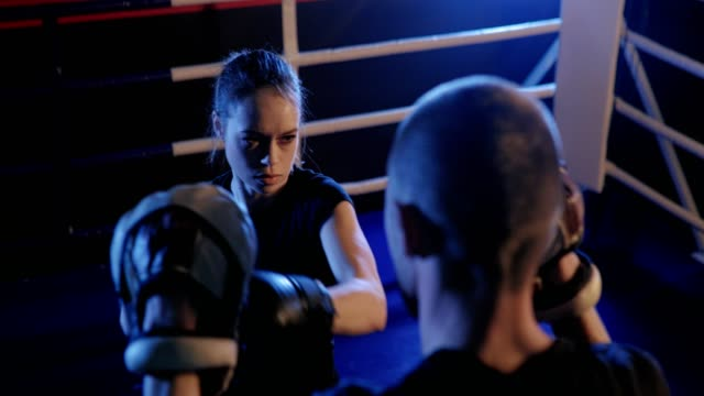 Athletic-woman-trains-her-punches-on-the-bag-which-is-held-by-her-partner-coach-Strong-and-gorgeous-woman-exercising-in-the-gym-
