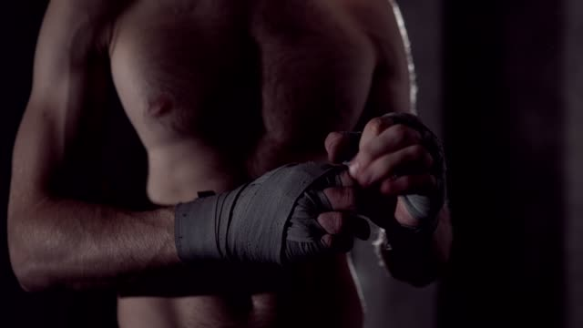 Male-boxer-wraps-his-hands-with-handwrap-professional-boxer-wrapping-bandages-on-his-hand-Fighter-wrapping-hands-with-boxing-wraps-in-the-gym