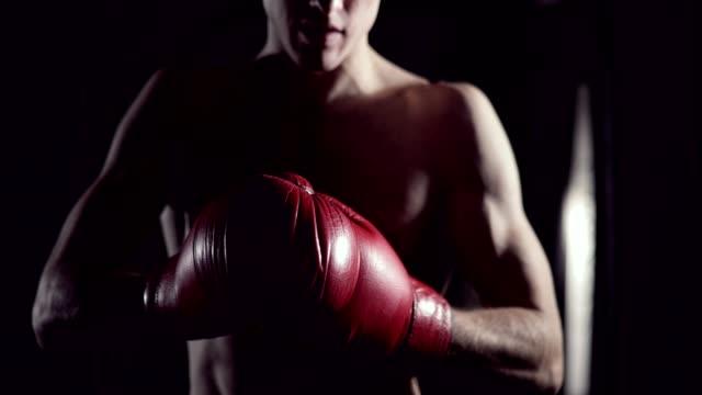Boxeador-se-pone-guantes-de-boxeo-Hombre-luchador-poniendo-los-guantes-en-cámara-lenta-Kickboxer-preparándose-poner-guantes-de-tren