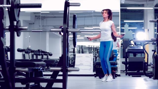 Mujer-sana-de-adultos-saltando-con-una-cuerda-de-salto-Cuerda-de-salto-femenino-en-gimnasio-Mujer-entrenando-en-el-gimnasio-ejercitándose-es-saludable